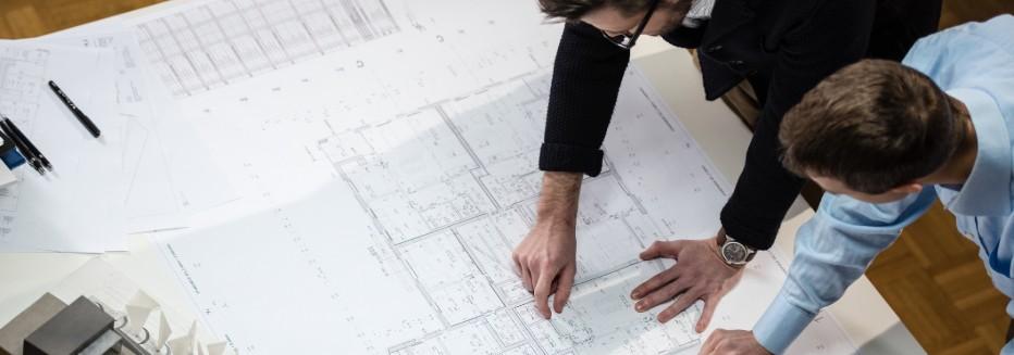 estudo de viabilidade técnica: pessoas analisando planta baixa de construção civil
